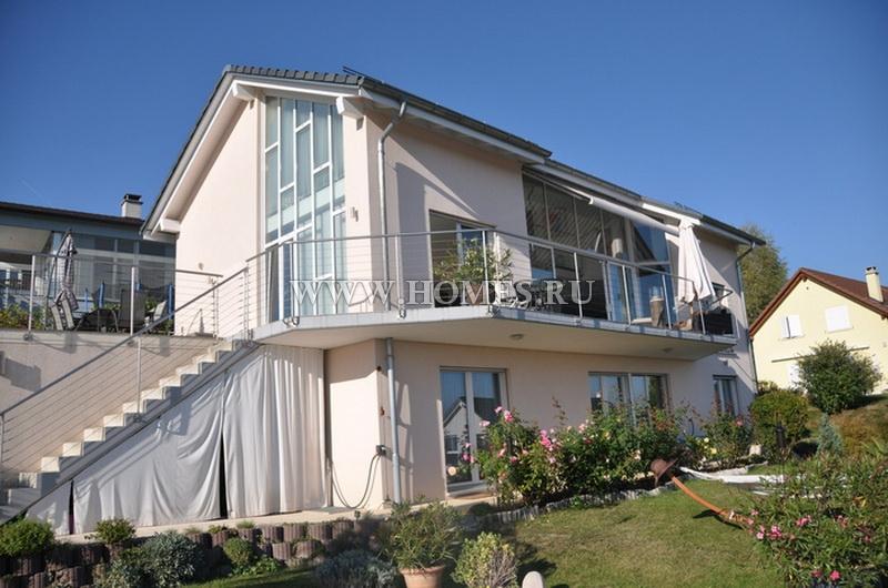 Современный дом с видом на озеро и горы
